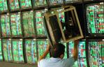 Un trabajador ajusta un televisor en una casa de comercio de valores en Taipei.